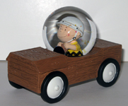 Charlie Brown in wooden soap box derby car Snowglobe
