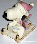 Snoopy and Woodstock sitting on sled with presents