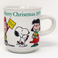 Peanuts gang holding Christmas articles Mug