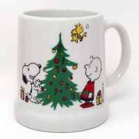 Snoopy and Charlie Brown stand looking at Christmas Tree Stein