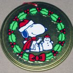 Snoopy sitting in wreath with snowman Round Metal Ornament
